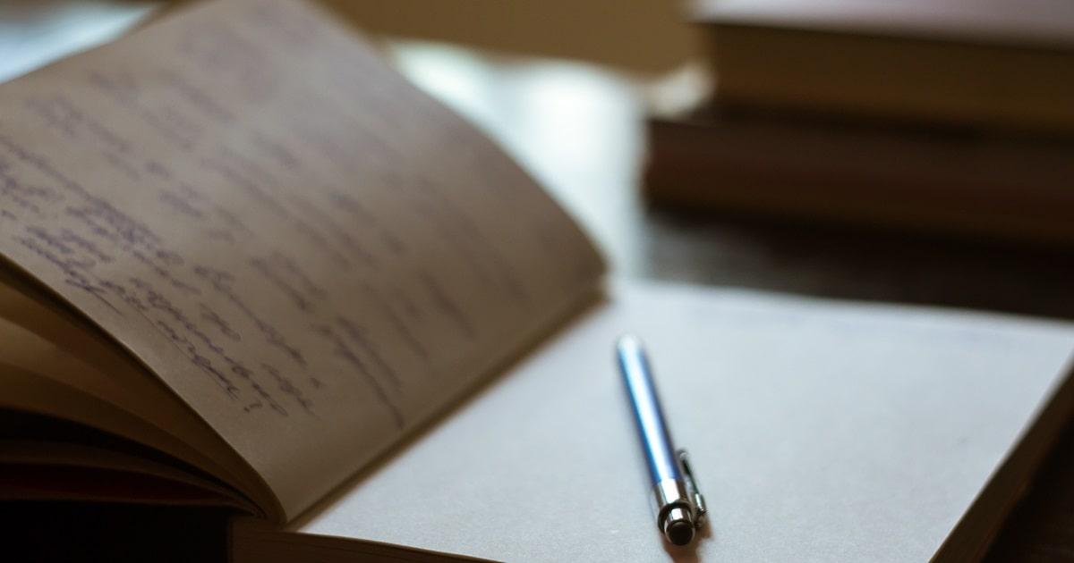 青いペンで手書きのメモ、背景の本でメモ帳を開く