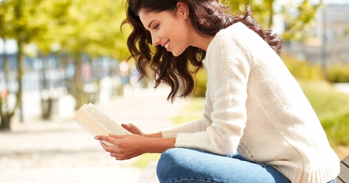 緑あふれる公園の遊歩道で本を読む女性