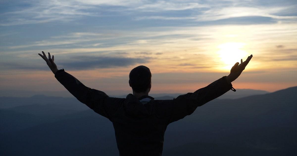 日没時に自分の成功体験と向き合い気分爽快になっている男性
