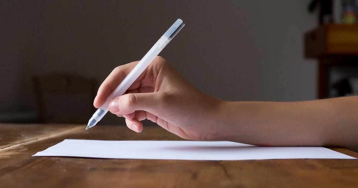 紙に手で何かを書こうとしてる様子