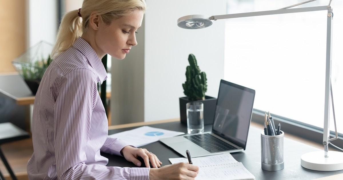 手書きで勉強する大学生、あるいは手書きで資格の勉強をする若いビジネスパーソン