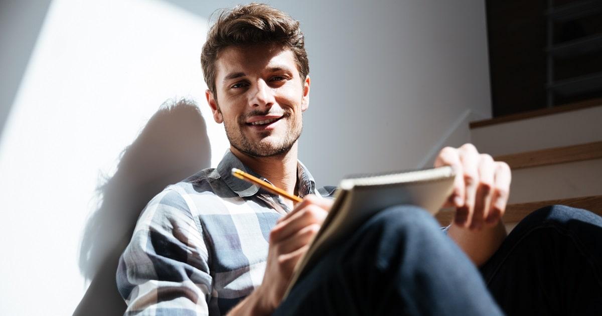 なんだか幸せそうな、階段に腰掛けノートに手書きする若い男性