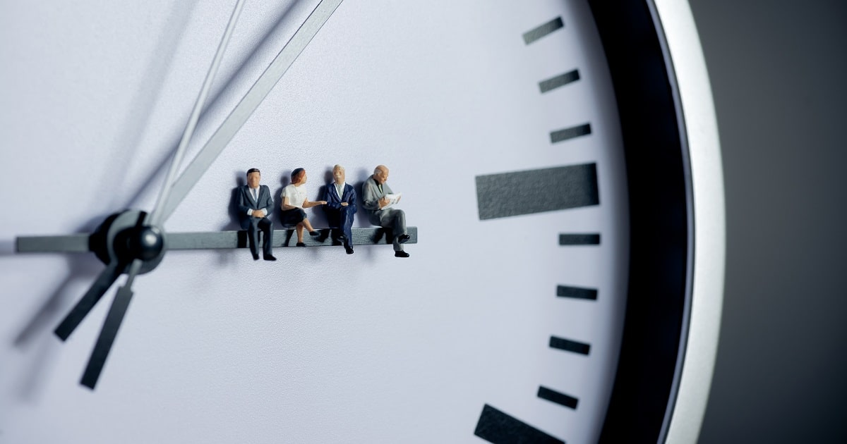 時計の針に腰かける小さなビジネスパーソンたち。スキマ時間活用の概念