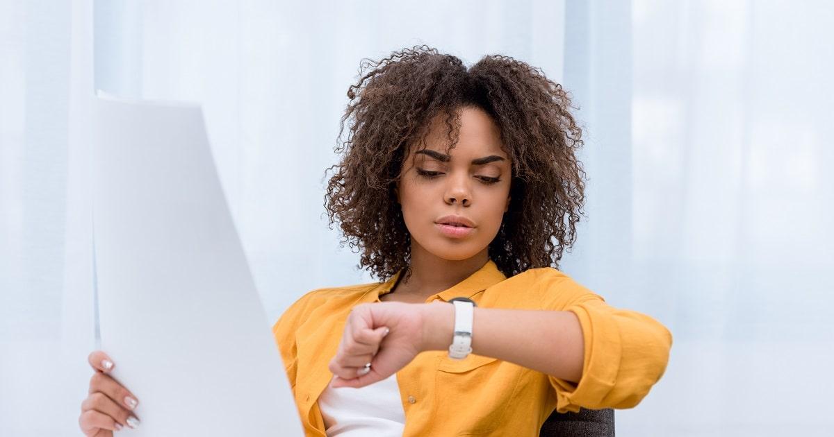 「ちょっと時間が空いたから資料をチェックしておこう」と時計を見ながら考えている女性