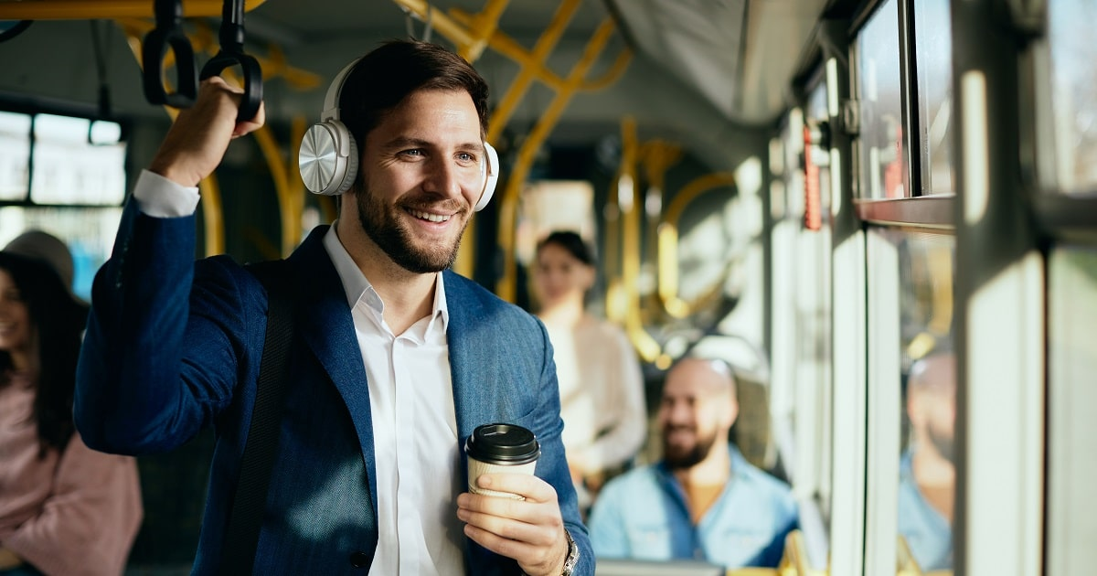 バス移動中の若いビジネスパーソンは、スキマ時間に飲み物片手に音楽を聴いて思いきりリラックス