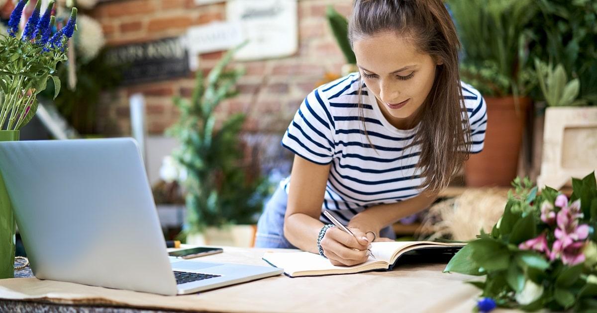 ノートに手書きする、ボーダーシャツを着た女性