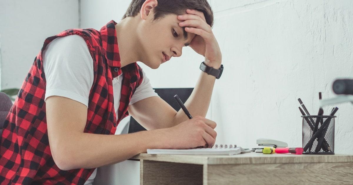 ノートに手書きして勉強する学生