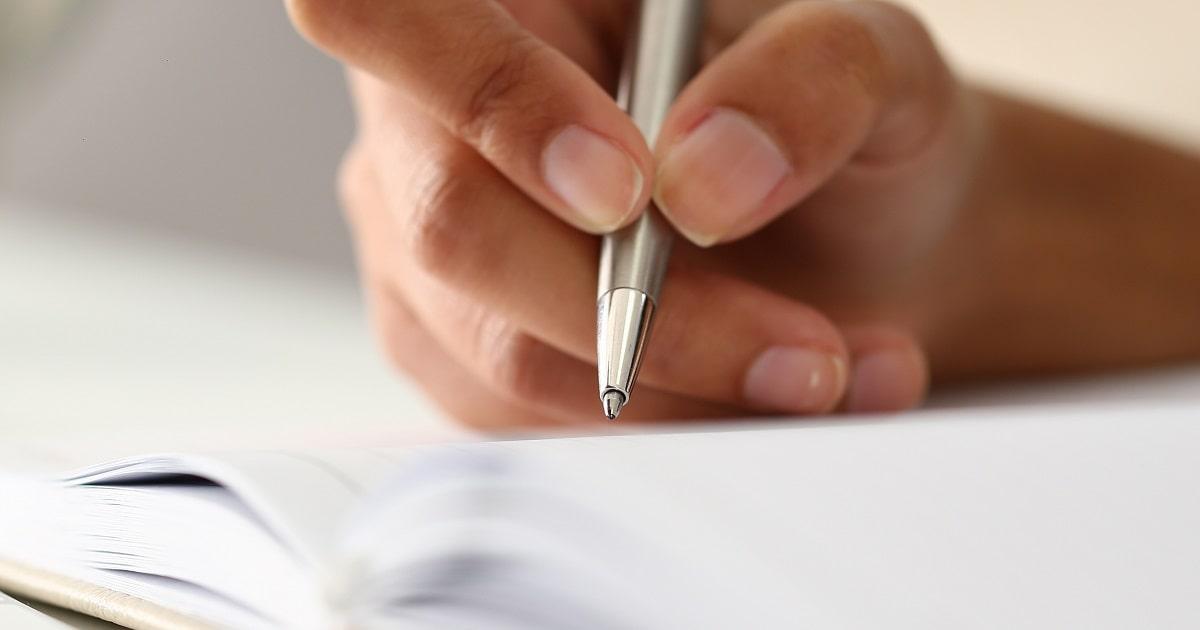 ノートに手書するビジネスパーソン