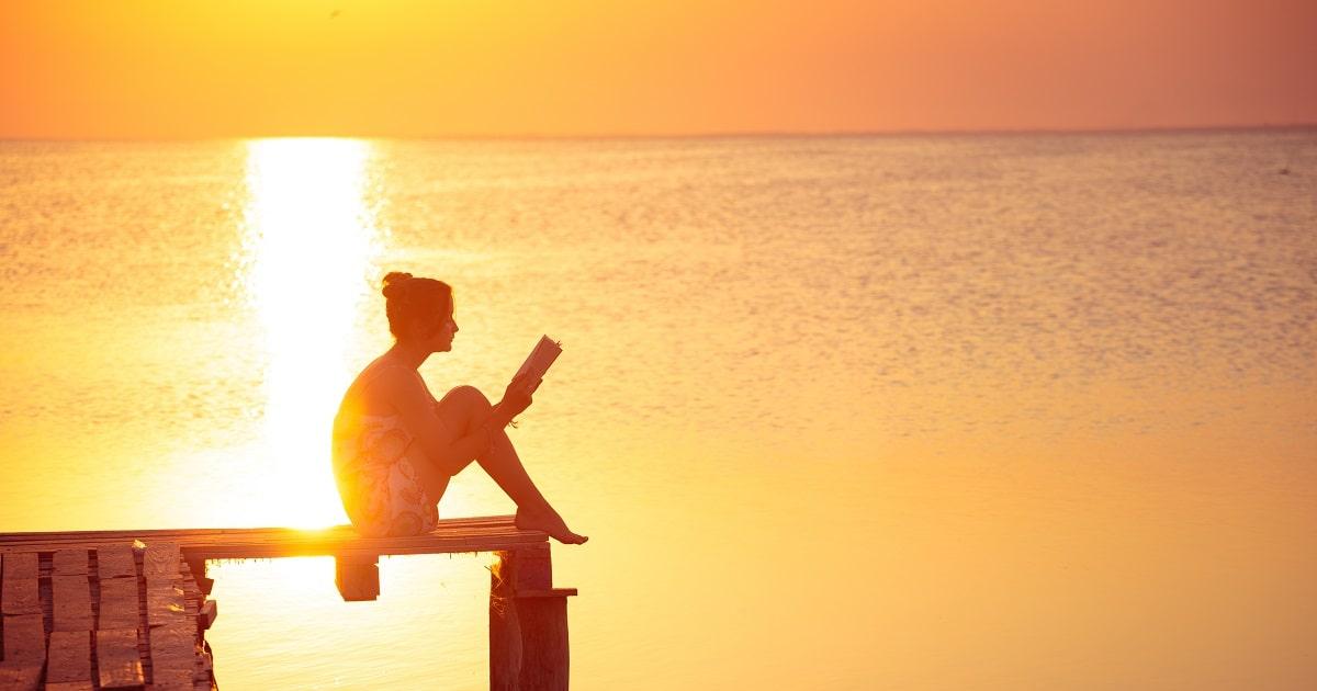 夕日を背景にひとり読書をする女性