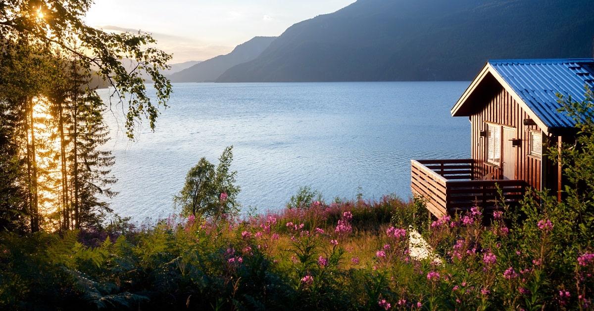 日没時に風光明媚な湖を見下ろすキャビンの画像