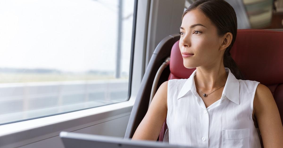 ノートブックを扱う手を止め、列車の外を眺めてボンヤリしているビジネスパーソン