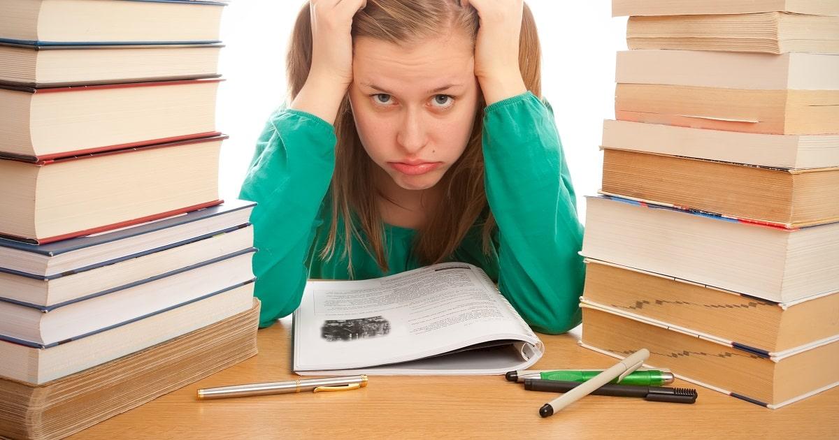 辞書の山に挟まれて、勉強の成果が出ないとふてくされている女性