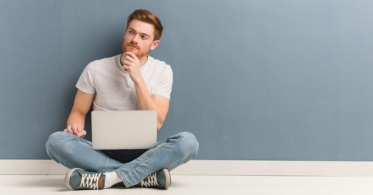 ノートブックパソコンを膝に起き、勉強について自問する男性