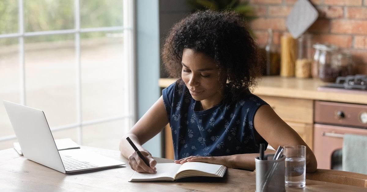 紙のノートに感情を書き出し、ストレスを感じた出来事に折り合いをつけている若いビジネスパーソン