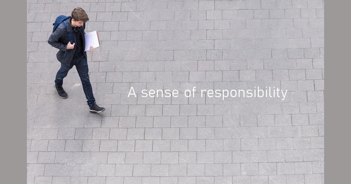 「A sense of responsibility」の文字と学校に向かう大学生