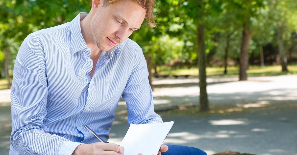緑に溢れる公園のベンチでセルフ・モニタリングノートをつける若い男性。