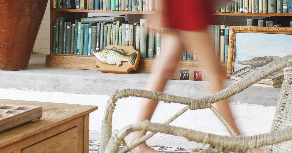 暗記科目を歩きながら勉強する女性。大きな本棚の前