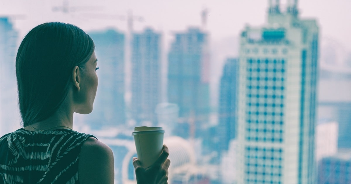 高層ビルに入ったオフィスの窓から、都会の景色を眺めるホワイトカラーの女性