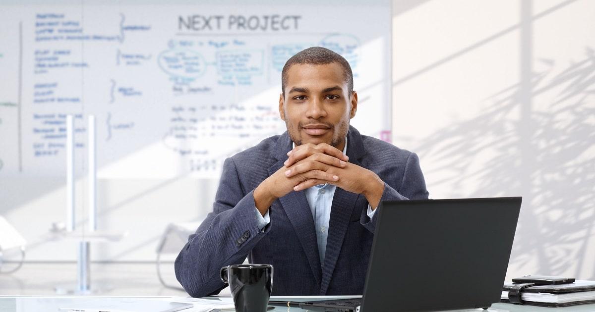 パソコンの前であごの下で手を組み、ゆったりと構えているビジネスパーソン