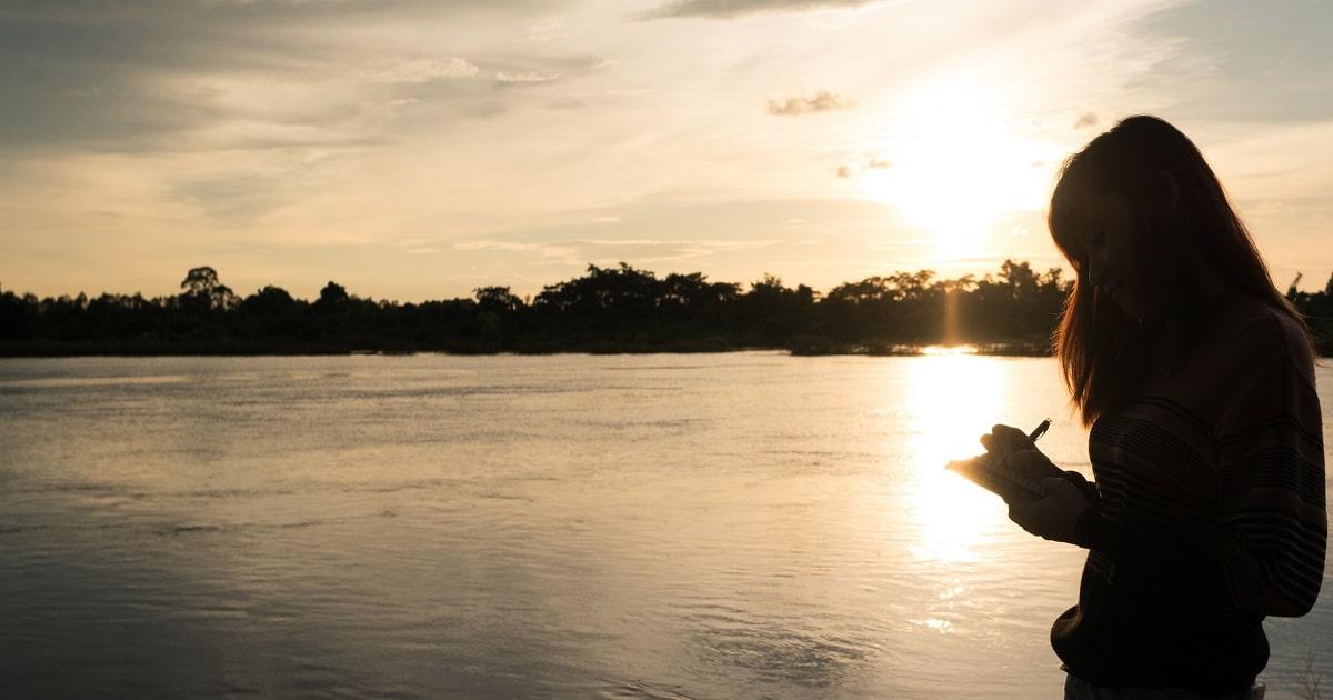 川沿いで、リラックスしながら1日を振り返り、1行日記を書く人物のシルエット