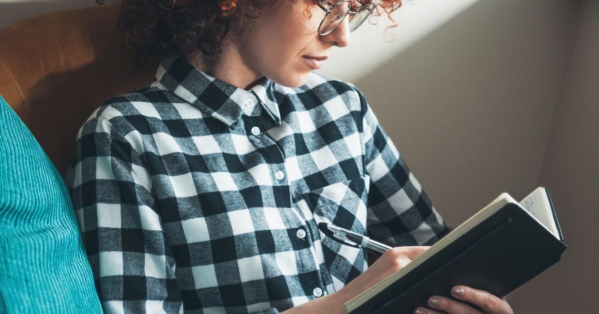 家でくつろぎながら、就寝前の「いいね!日記」を書く女性