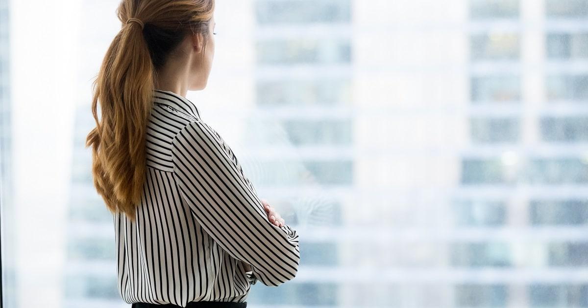 窓の外を眺めるビジネスパーソン