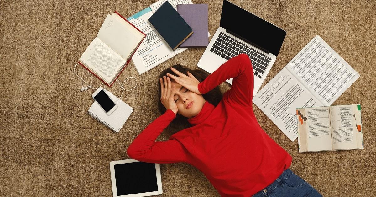 「もうダメだ」と勉強を投げ出したくなっている赤いニットの学生あるいはビジネスパーソン