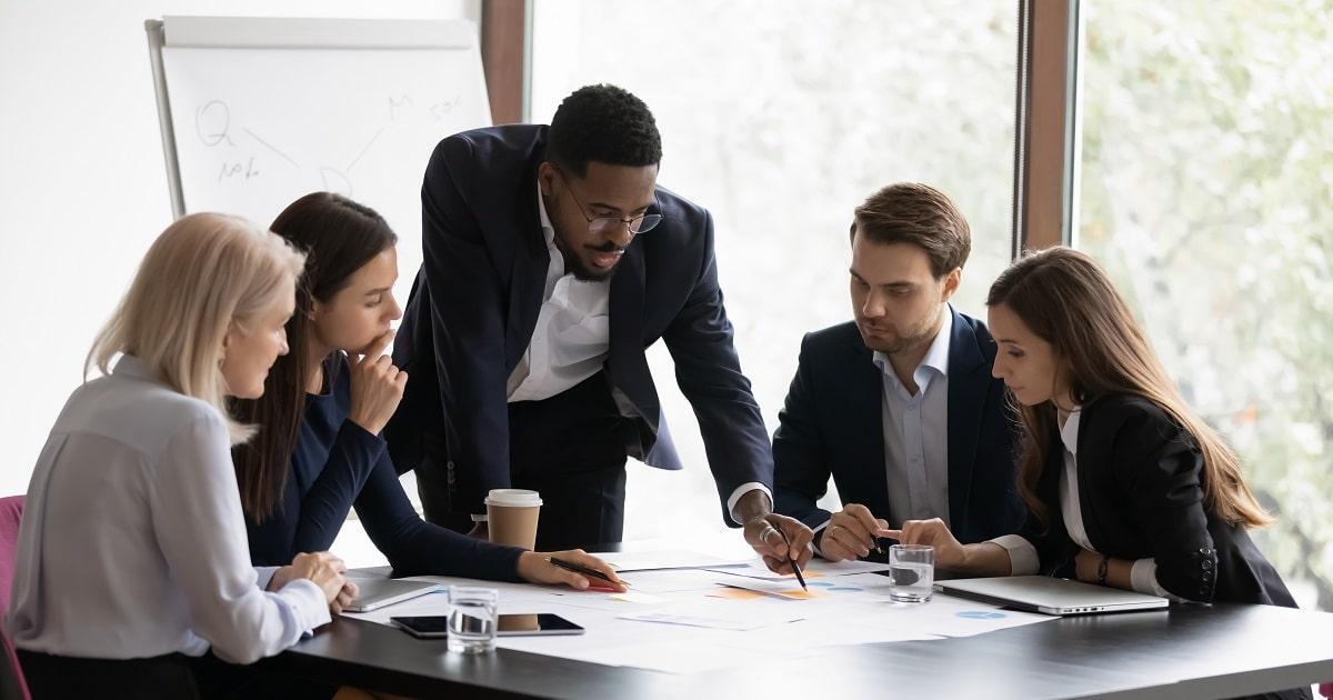 オフィスで多様なチームとミーティングを行う若きリーダー