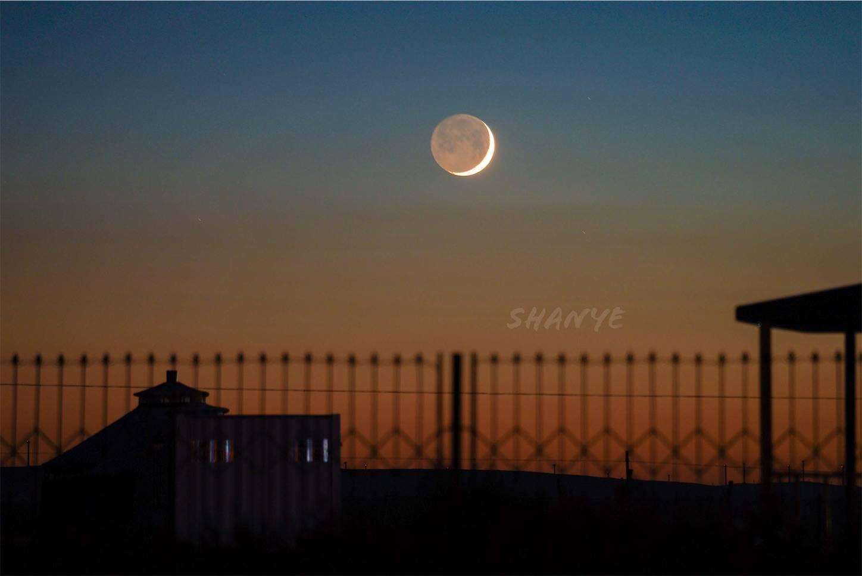 草原の夕日に浮かぶ満月