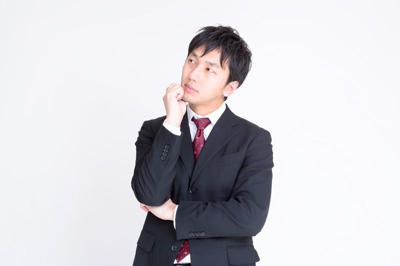 考えるスーツ姿の男性の画像