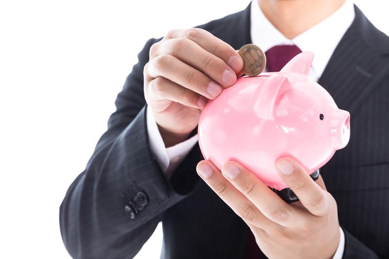貯金箱にコインを入れる人の画像