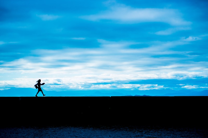 青空の下を歩く女性のシルエット写真