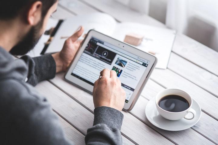 タブレットでニュース記事を読んでいる男性の写真
