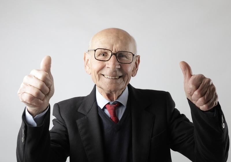 笑顔で親指を立てる高齢男性の写真