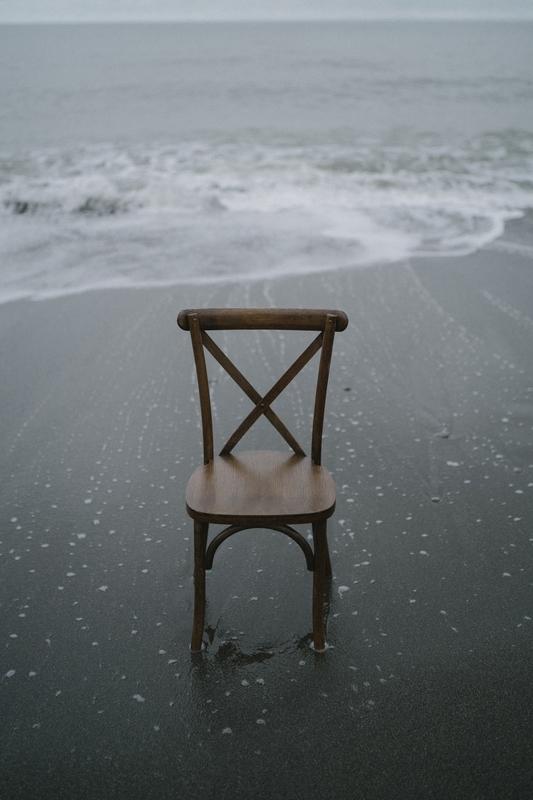 曇天の浜辺にイスだけが佇んでいる写真