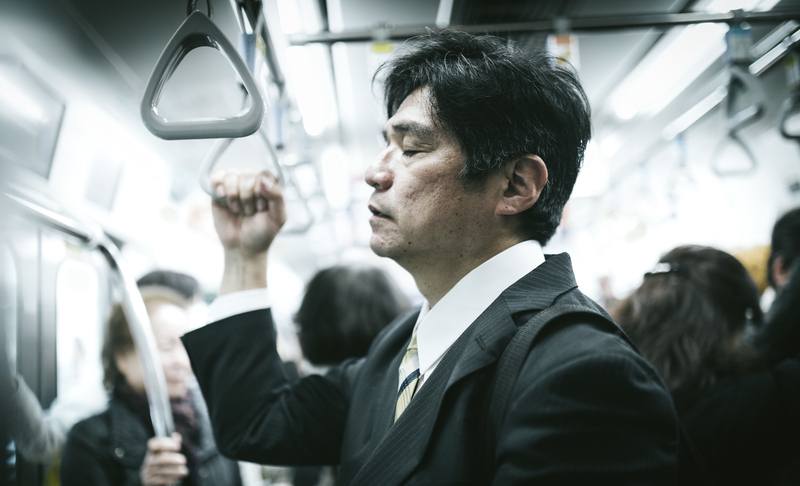 電車に乗っているお疲れサラリーマンの写真