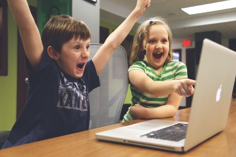 パソコンの画面を見つめて喜ぶ子どもたちの画像