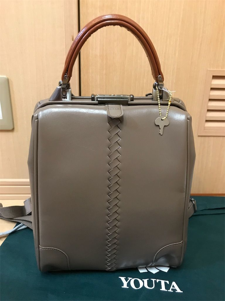 YOUTA(ヨウタ)バッグのダレスリュック縦型XSサイズ(トープ色)。ロングタイプのハンドル(キャメル)にカスタマイズ。