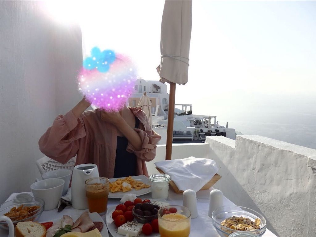 ギリシャ新婚旅行で宿泊したサントリーニ島イアのおすすめ洞窟ホテル「ラ ペルラ ヴィラズ アンド スイーツLa Perla Villas and Suites」一番お安いジュニアスイート客室の様子。テラスにてパラソルの下でエーゲ海の絶景を眺めながら朝食