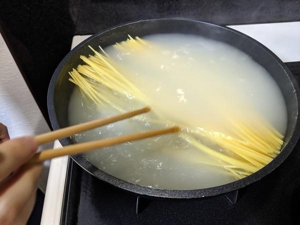 沸騰した湯の中でスパゲティをよくほぐします