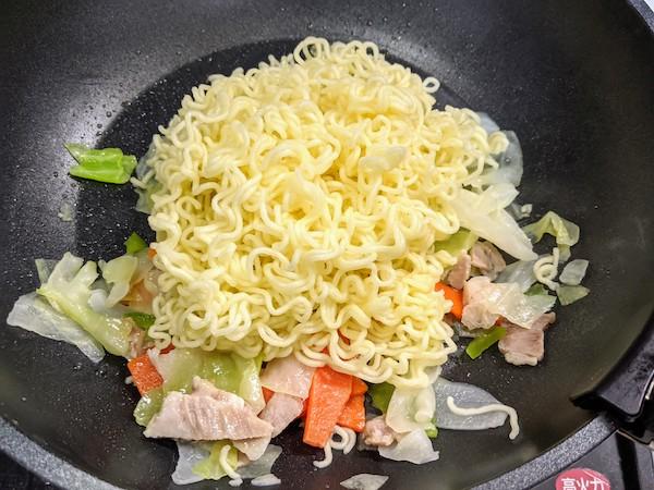 肉入りカット野菜が解凍されて全体に火が通ったら麺を入れます