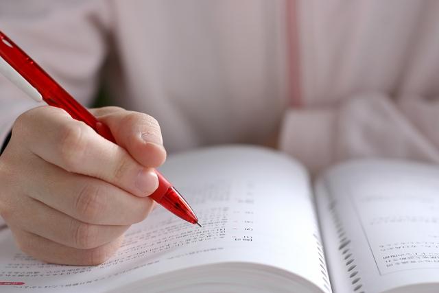 ノートを開いて線を引く子供の画像