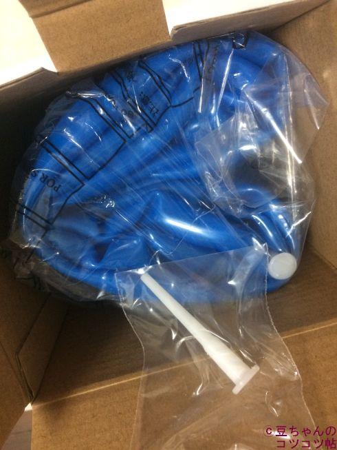 ダイソーのバランスボールの箱を開封するところ。青いバランスボールが薄いビニールに包まれています