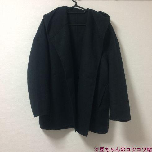 黒いハーフコートが壁にかかっている画像