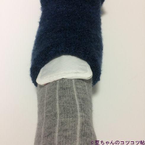 グレーの靴下を履いた足の甲にカイロをはさみ、その上から靴下を重ねているところの画像