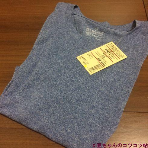 ブルーグレーのTシャツが床の上に畳まれた状態で置いてある