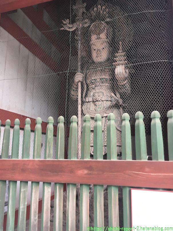 柵の奥に仏像が立っている画像