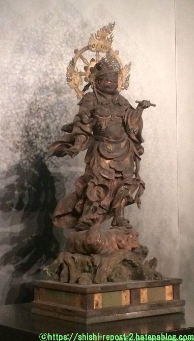 筆と巻物をもつ仏像の写真