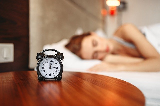 眠る女性と目覚まし時計