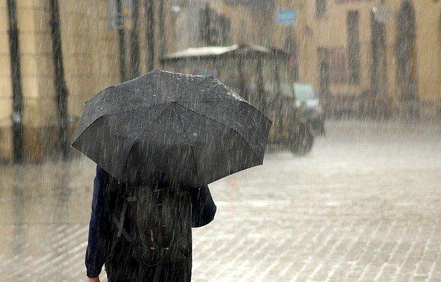 大雨で傘をさす男性